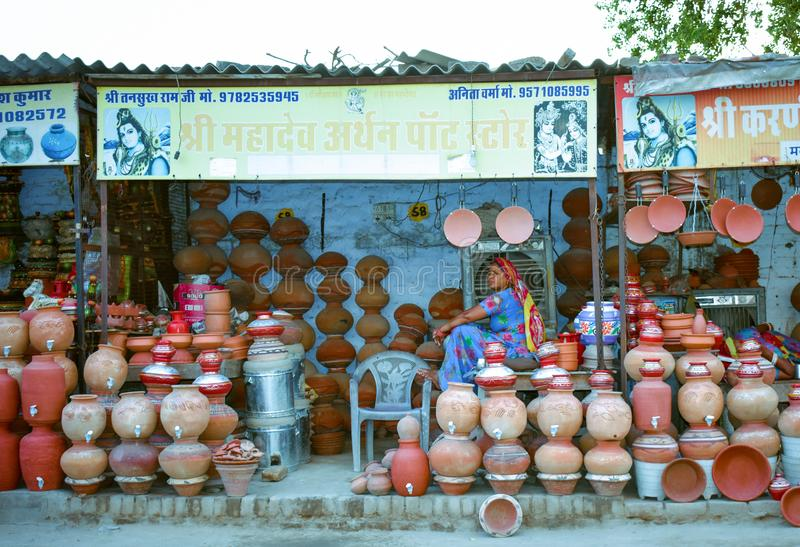 A lady sitting in local market and selling her water pots in indian summer stock image