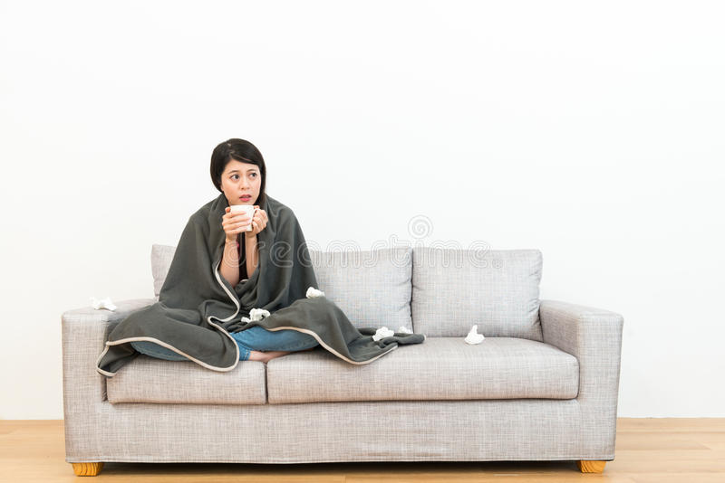 Lady sitting on sofa couch and holding hot water. Pretty attractive lady sitting on sofa couch and holding hot water for warming body when she coughing a cold stock images