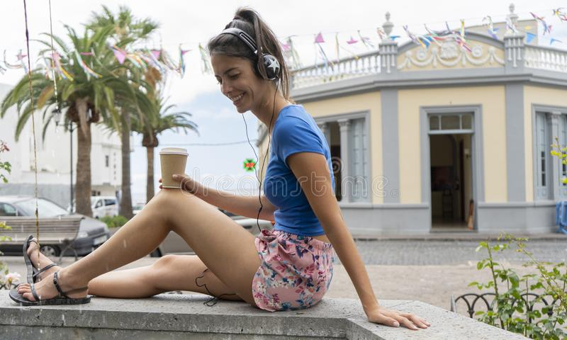 Lady sitting in stone fountain listening a song with earphones drinking a takeaway coffee cup. Dark hair Teenager in flips flops royalty free stock photography