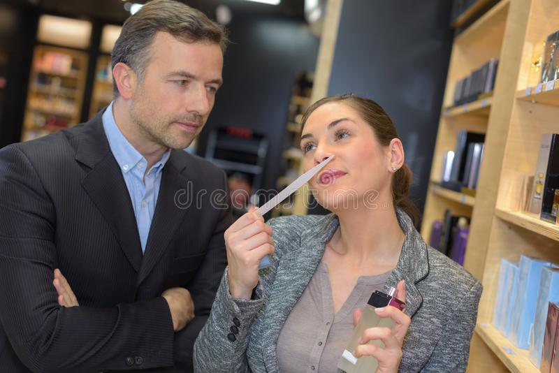 Lady smelling perfume man looking on with serious expression stock photos