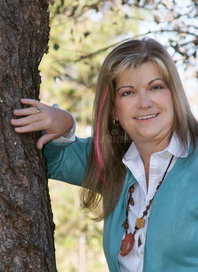 lady som poserar nära den nätt treen arkivfoton