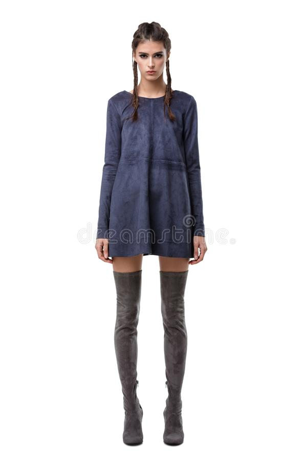 Lady standing in dark blue suede dress and knee high boots on white background isolated royalty free stock photo