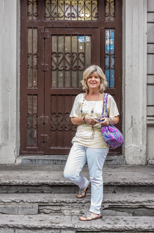 Lady standing on porch steps stock image