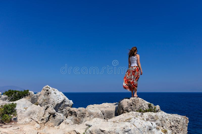Lady stands on the edge of a stone cliff and looks into the distance to the sea horizon stock photos