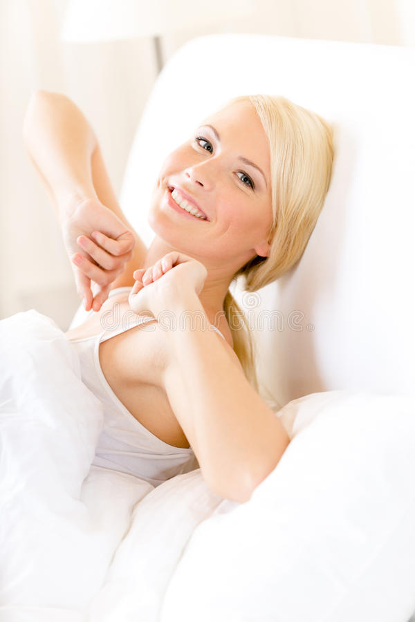 Lady Stretches Herself Lying In Bed Royalty Free Stock Photography