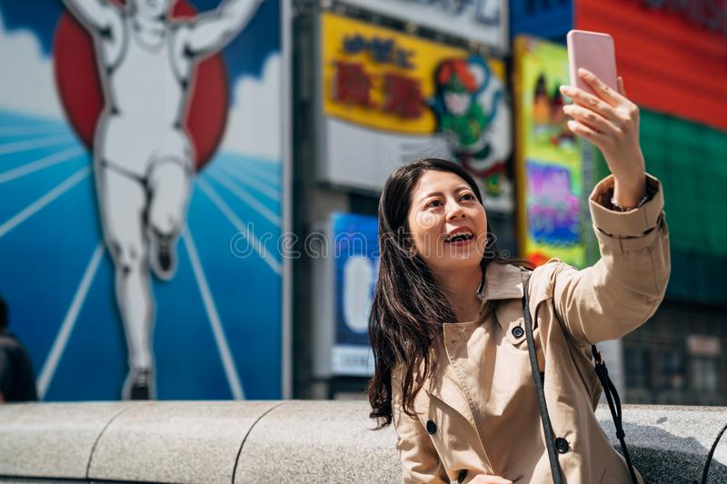 Lady taking selfie with nippon runner sign royalty free stock photography