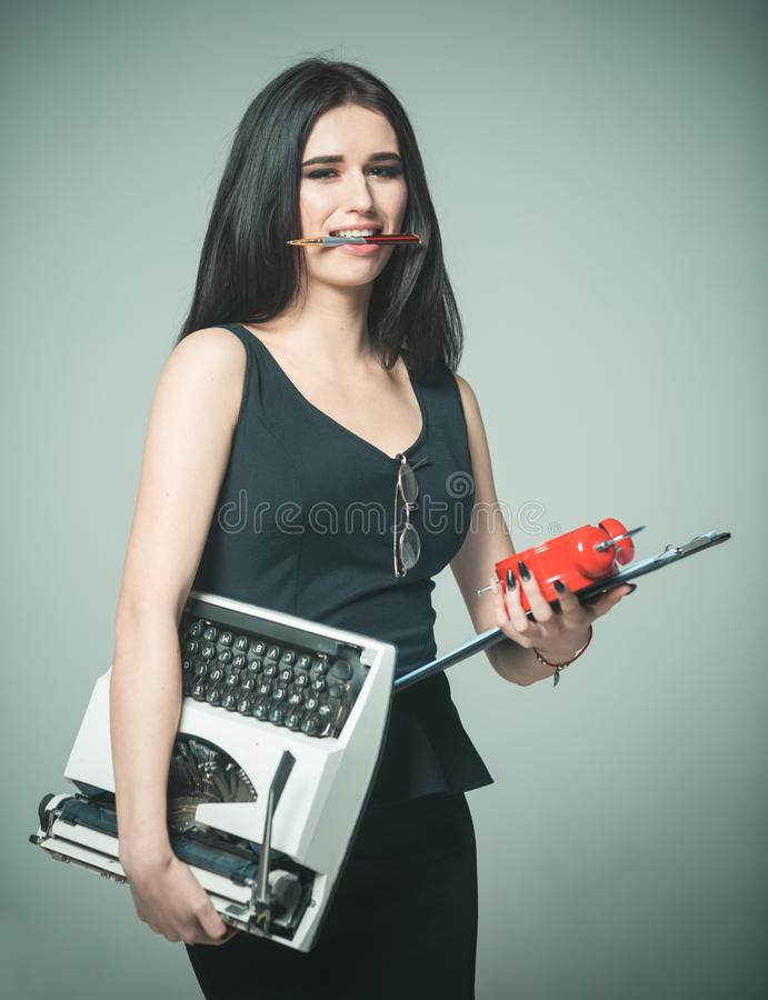 Lady teacher carries typewriter alarm clock and schedule. Multitasking concept. Lady successful multitasking. Girl holds stock images
