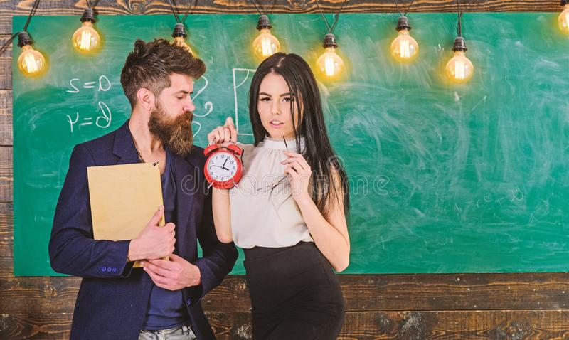 Lady teacher and strict schoolmaster care about discipline and rules in school. Man with beard hold book and girl. Teacher holds alarm clock, chalkboard on stock photography