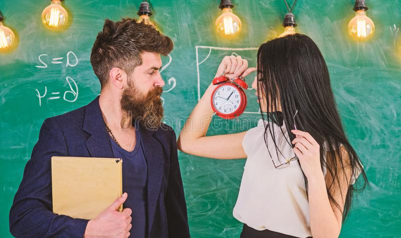 Lady teacher and strict schoolmaster care about discipline and rules in school. School rules concept. Man with beard. Hold book and sexy girl teacher holds royalty free stock image