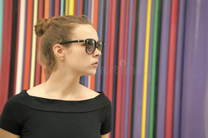Lady tender mysterious face with black eyeglasses in front of striped colorful wall in paris. Woman stylish appearance royalty free stock images
