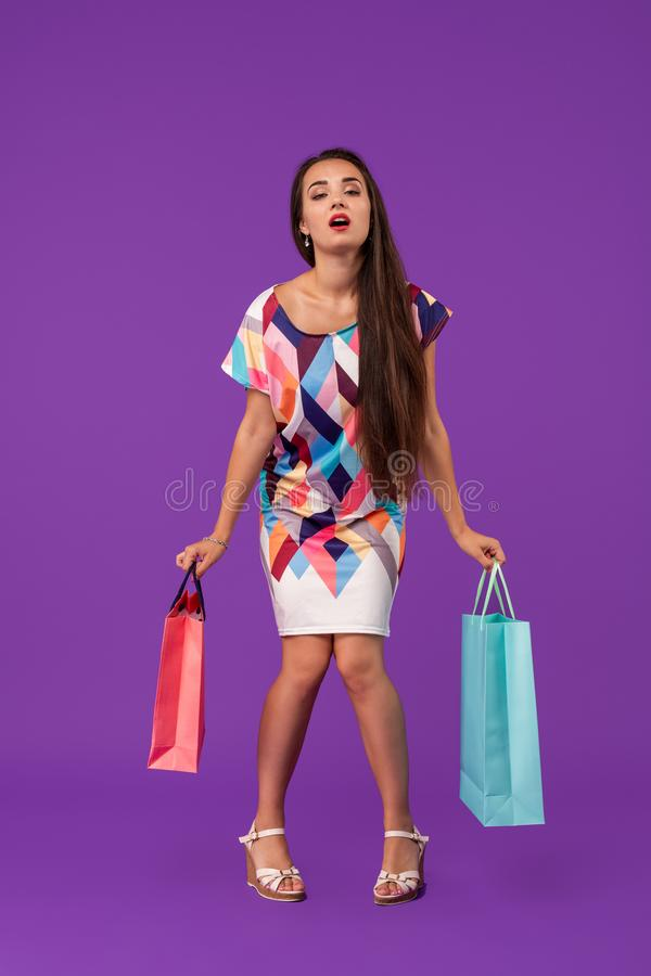 Lady with tired face. Girl stands on purple background holding shopping bags. Woman wears fashionable dress. Money and shopping concept. Lady with tired face stock image