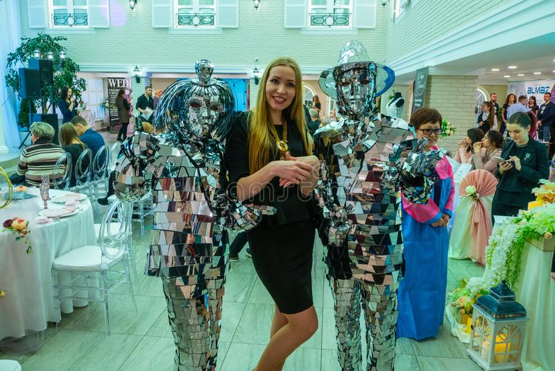 Lady the toastmaster is posing for the camera between the dansers in reflecting suits. At the Wedding hassle 2019 exhibition took place in Kirov, Russia stock photo