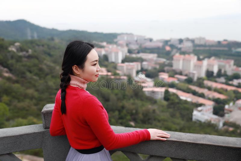 Lady tourist standing on a rock on the top of mountain and admire the view , Xiamen, China stock image