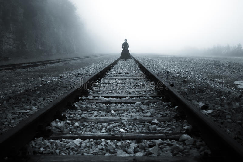Lady at train rail in the mist. Horror Scene of a Scary Woman royalty free stock images