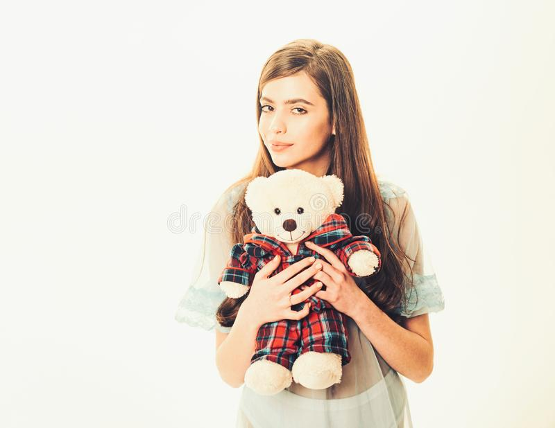 Lady in transparent blue nightie holds teddy bear in hands, white background, copy space. Girl with plush bear toy. Wishes sweet dreams. Sweet dreams concept stock image