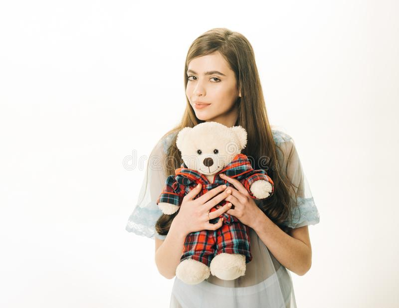 Lady in transparent blue nightie holds teddy bear in hands, white background, copy space. Girl with plush bear toy. Wishes sweet dreams. Sweet dreams concept royalty free stock photos
