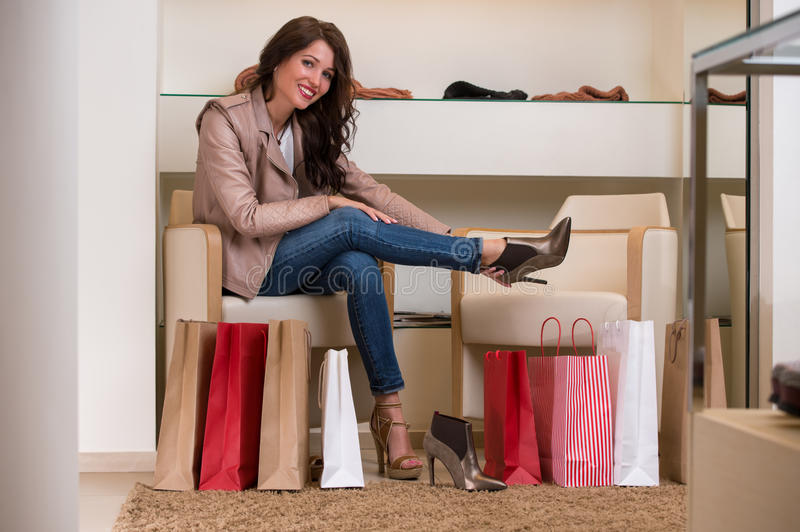 Lady trying on several pairs of new shoes in store. Image of lady trying on several pairs of new shoes in the store royalty free stock photography