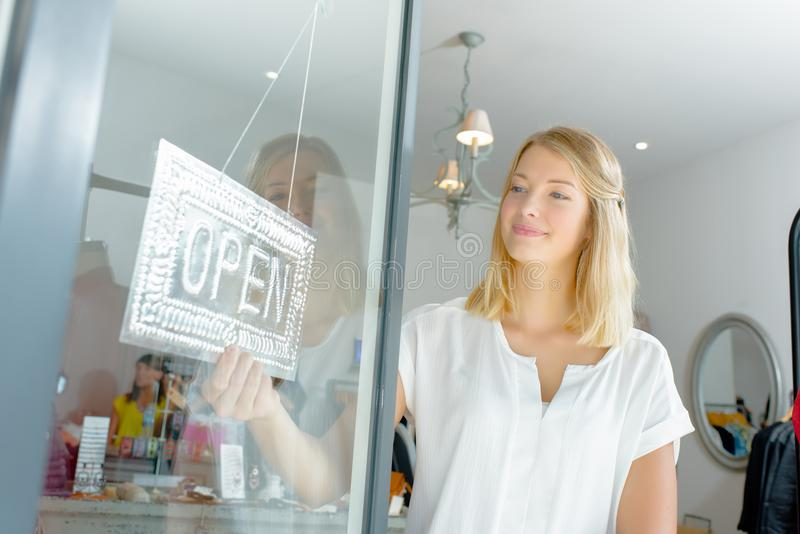 Lady turning shop sign to open. Achievement stock photo
