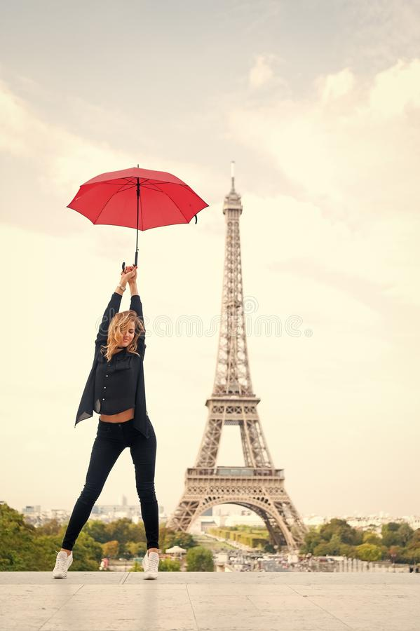 Lady with umbrella posing in front of Eiffel Tower, sky background. Lady tourist sporty and active walks in Paris city royalty free stock photography