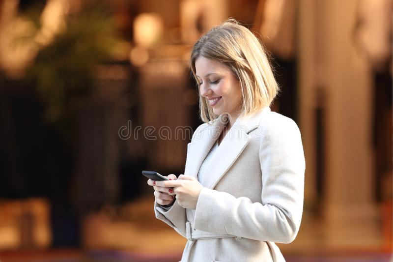 Lady uses a smart phone in the street. Of a commercial centre stock photos