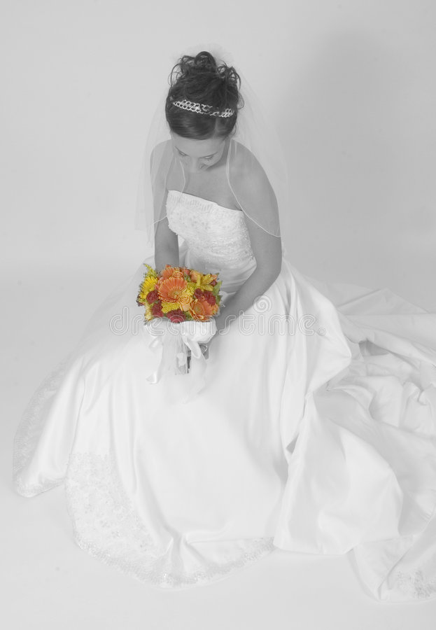 Lady in waiting. Bride in black and white holds colorful bouquet of flowers royalty free stock photos