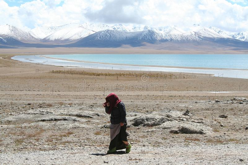 lady walking alongside the road in tibet with beautiful mountains in the background royalty free stock photo