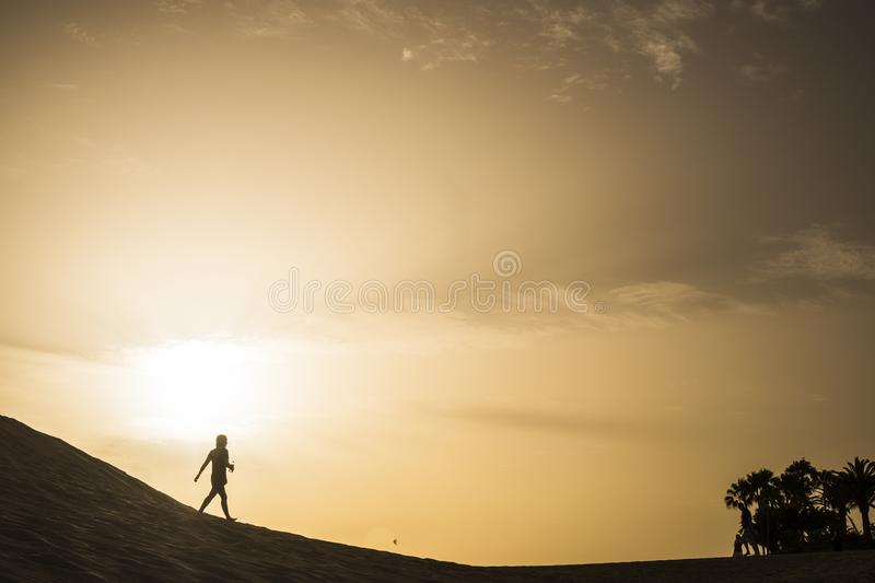 Lady walking on a dune desert in maspalomas canary islands during a golden smazing beautiful sunset with orange and yellow colors royalty free stock image