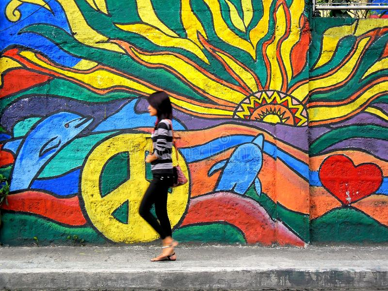 A lady walking past a street wall art. Photo of A lady walking past a street wall art in quezon city, philippines in asia royalty free stock photography