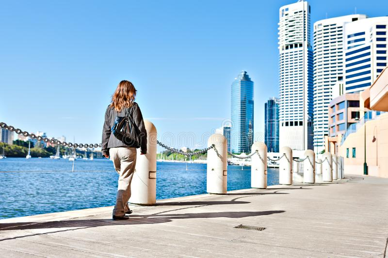 Lady walks on the street near to the river royalty free stock image