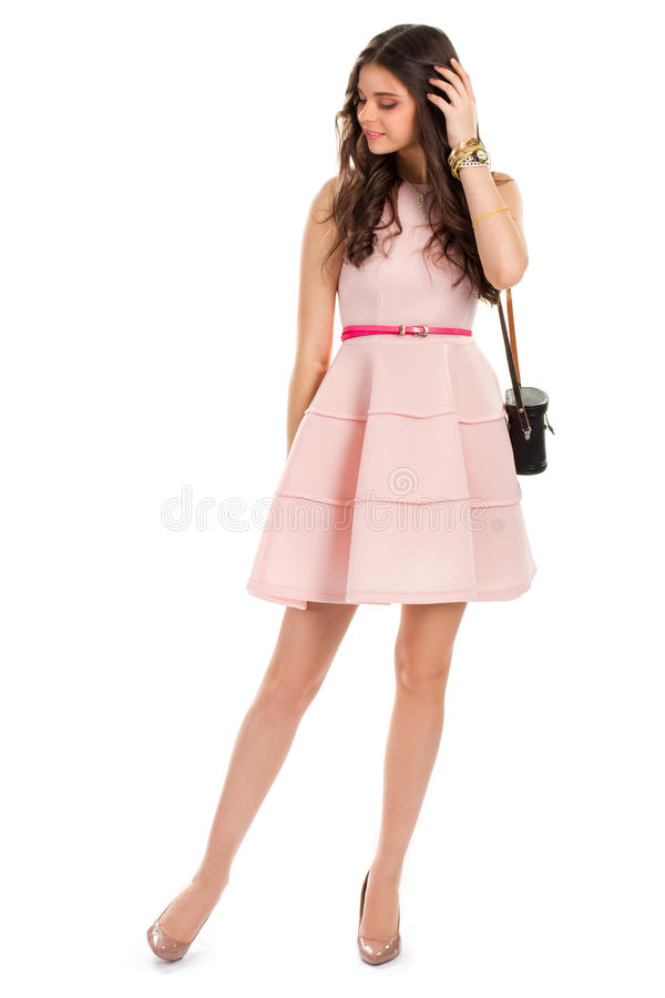 Lady wearing beige heel shoes. Salmon dress with black purse. Young model in cocktail dress. Brand new stylish apparel stock photo