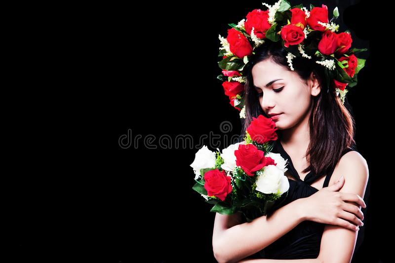 The lady is wearing black dress with rose crown on her head,holding rose bouquet in arms,posing at the right side of background royalty free stock images