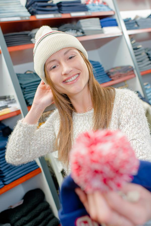 Lady wearing bobble hat in clothes shop. Accessories stock images