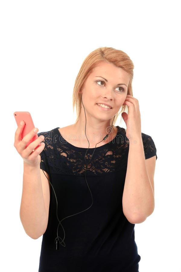 Lady wearing earphones connected to smartphone royalty free stock image