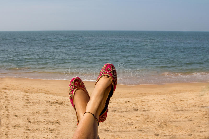 A lady wearing a pair of pink traditional Indian women`s shoes jutis at the Anjuna beach in Goa, India. A lady wearing a pair of traditional Indian women`s shoes royalty free stock images