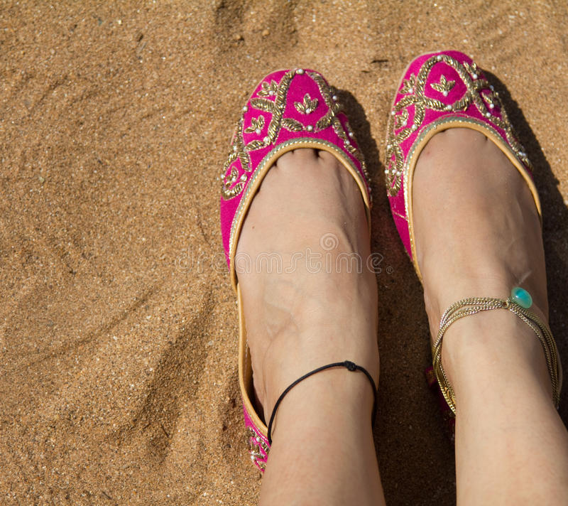 A lady wearing a pair of pink traditional Indian women`s shoes jutis at the Anjuna beach in Goa, India stock photography