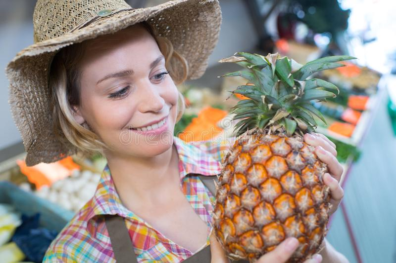 Lady wearing straw hat and holding pineapple stock image