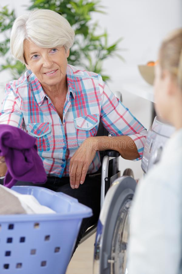 Lady in wheelchair talking to help assistant royalty free stock photography
