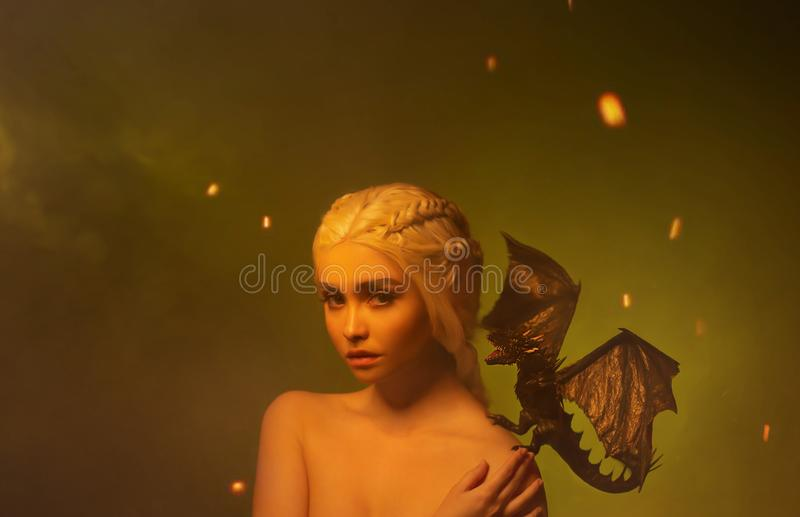 Lady with white braided hair and little dragon bare shoulder. royalty free stock photos