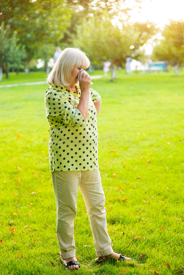 Lady wiping eye with handkerchief. royalty free stock photography