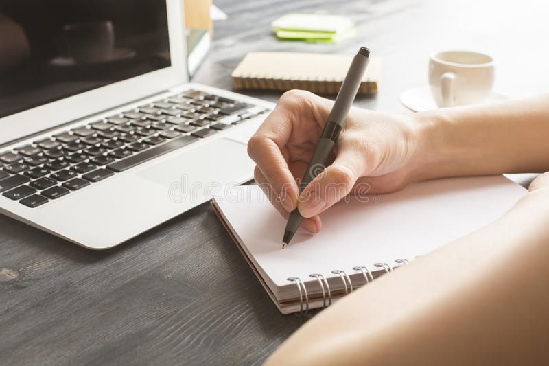 Lady writing in notepad. Close up of lady writing in notepad placed on wooden desktop with blank laptop, supplies and other items. Mock up royalty free stock photography