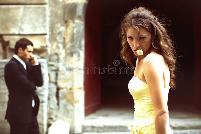 Lady in yellow dress poses with rose in her mouth while man talk. Lady in yellow dress poses with rose in her mouth while men talk on the phone on the background royalty free stock photography