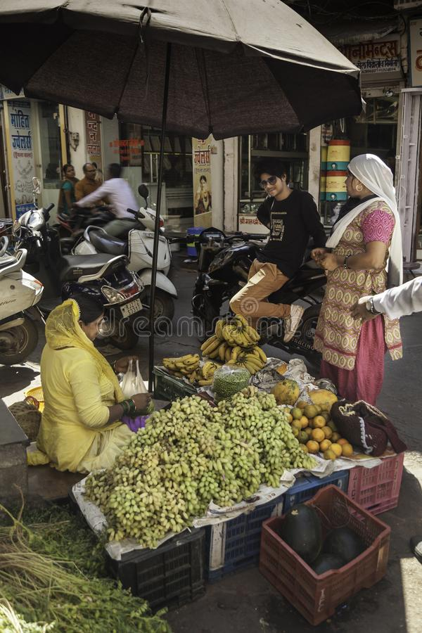 Lady in Yellow Sari Chats to Customers stock photo