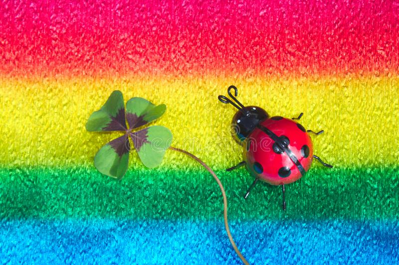 Ladybird and lucky clover on colorful crepe paper. The picture shows a ladybird and lucky clover on colorful crepe paper stock image