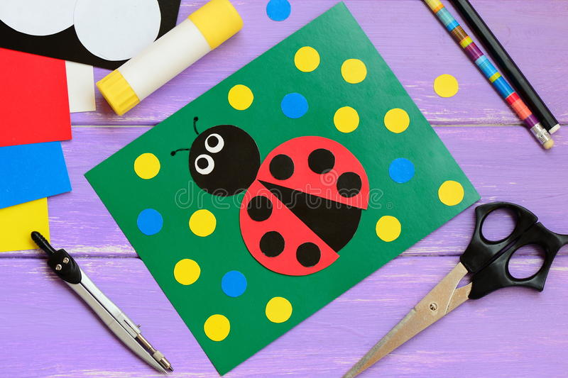 Ladybug card. Ladybug card, scissors, glue stick, pencil, marker, paper set, compass on a wooden table. Paper and glue crafts. Developing motor skills. Paper stock photo