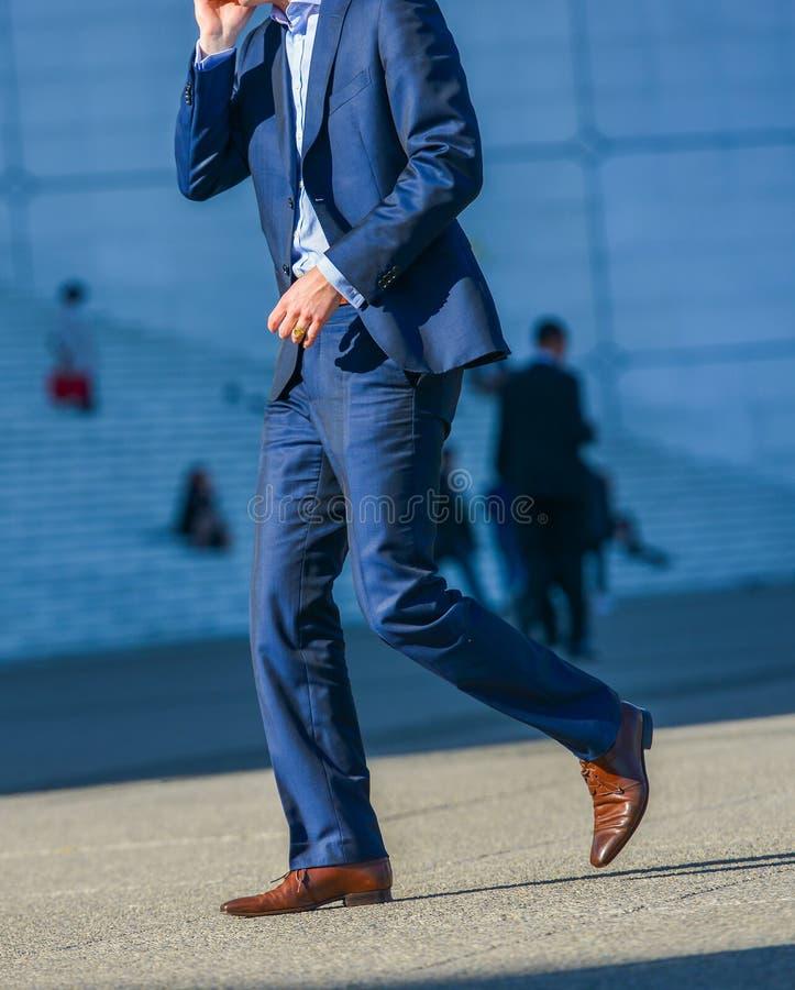 Laförsvar, Frankrike April 09, 2014: sidosikt av affärsmannen som går i en gata Han bär en mycket elegant blåttdräkt och en hög q arkivbild