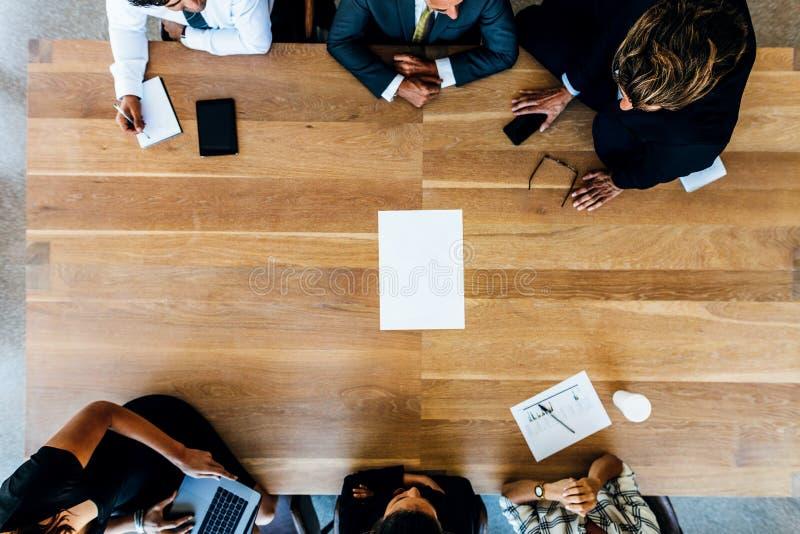 Lag av affärsfolk runt om tabellmötet royaltyfria foton