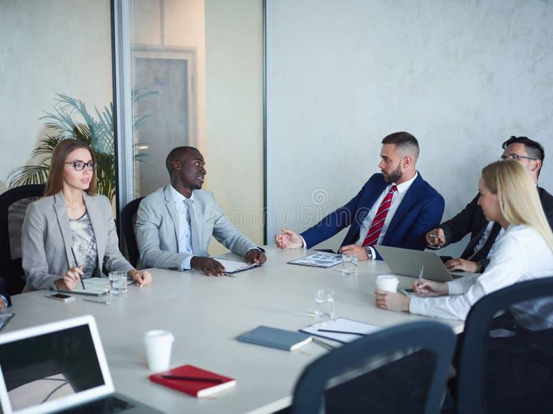 Lag av affärsfolk som möter i konferensrum arkivfoto
