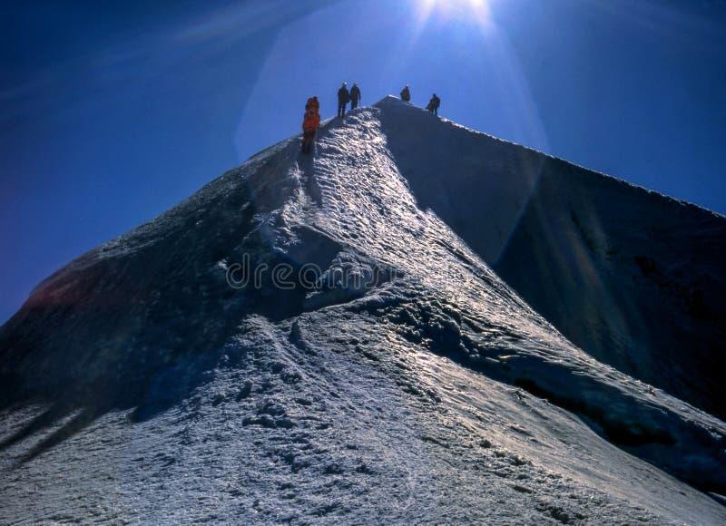 Lag av alpinister på en bergöverkant royaltyfri bild