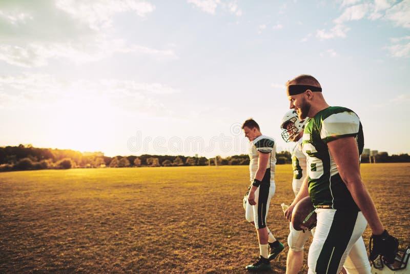 Lag av amerikanska fotbollsspelare som går av ett sportfält royaltyfri fotografi