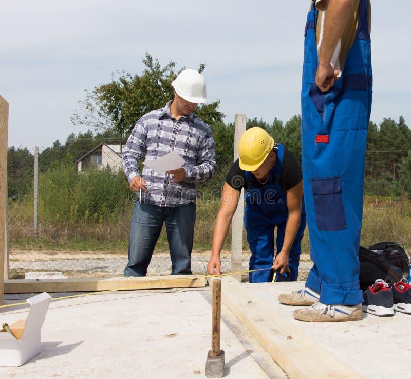 Lag av arbetare på en konstruktionsplats arkivbild